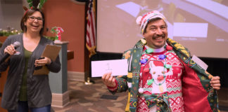 The UTRGV School of Medicine held its annual Ugly Sweater Contest, pitting faculty and staff from the Harlingen and Edinburg campuses against each other for the right to brag about having the ugliest holiday sweater, hands down. The SOM also collected gifts for families they are sponsoring in the Indian Hills neighborhood near Mercedes. Here, sweater contest champion Vicente Reyna proudly struts his stuff as the overall contest winner, to the amusement of Nina Jimenez, from the Graduate Medical Education department. (UTRGV Photo by David Pike)