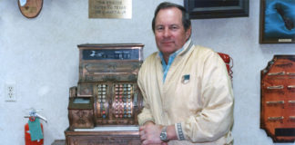 Joe LaMantia, Jr. next to an antique cash register. If was his preference for this picture to be taken next to the cash register. Photo taken on July 1988 and published in Texas Border Digest August 1988. Photo by Roberto Hugo González.
