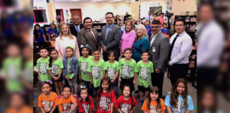 """Cynthia Rodriguez, principal, Sanchez Elementary School; McAllen Chief of Police Victor Rodriguez; City of McAllen Dist. 2 Commissioner Joaquin """"J.J."""" Zamora; Dr. J. A. Gonzalez, McAllen I.S.D. Superintendent; Alexandra Molina, McAllen I.S.D. Child Nutrition Services Director; Kate Horan, McAllen Public Library Director; Conrado Alvarado, McAllen I.S.D. School Board Member; and Jacob Martinez, McAllen I.S.D. transportation director, pose with students of Sanchez Elementary School after today's Mcallen Summer Feeding program was announced. There are 57 sites, including schools, libraries, parks, police substations, community centers, religious facilities and youth organizations sites and 15 bus routes that will provide meals to anyone in McAllen throughout the summer, beginning June 4. To find summer feeding locations, go to the McAllen ISD website (mcallenisd.org) or City of McAllen website (mcallen.net). You can also dial a state hotline number (2-1-1) to get locations near you. Or, send a text. Type the word """"Foodtx"""" and send to 877-877. #mcallensummerfeeding2018"""