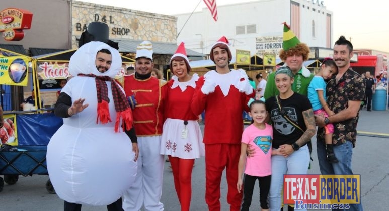 A family stops to take a photo with live characters including a snowman, toy soldier, elves, and Buddy the Elf.