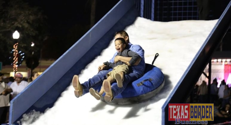 A father shoots down the snow slide with his son, who is seen laughing on the way down.