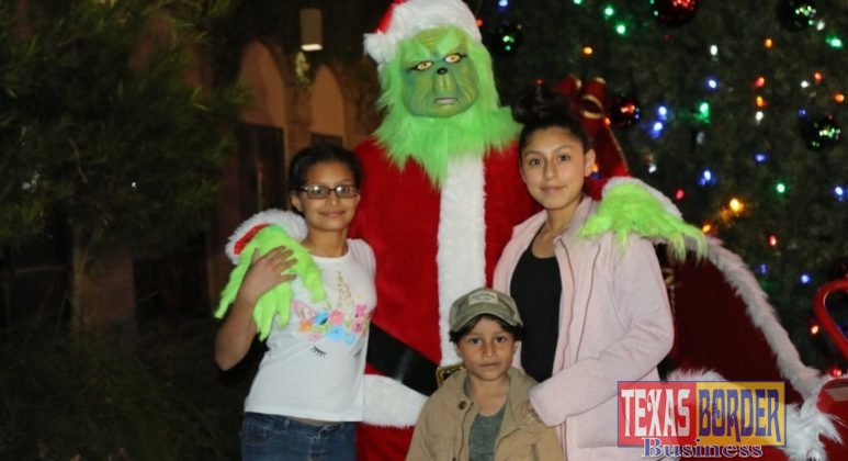 Children take a photo with one of the many live characters of the evening, The Grinch.